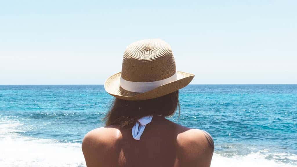 Woman wearing hat looking out at the water - Serendipity Anna Maria