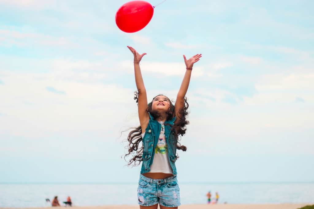 A girl jumping for a balloon on Anna Maria Island.